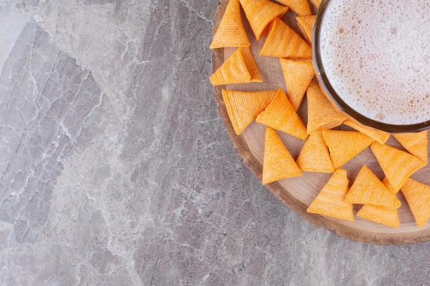 Croustilles croustillantes avec bière froide sur morceau de bois
