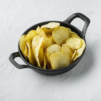 Croustilles croustillantes. tranches de pomme de terre dans une poêle en fonte