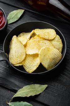 Croustilles croustillantes. tranches de pomme de terre, rôties au sel de mer, sur bois noir