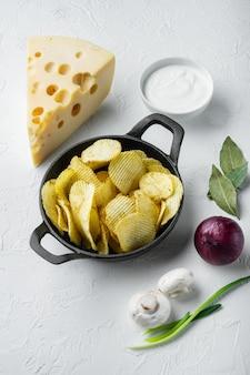 Croustilles croustillantes. tranches de pomme de terre rôties au sel de mer, garnies de fromage et d'oignon