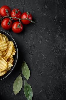 Croustilles croustillantes. tranches de pomme de terre, rôties avec du sel de mer, sur table en pierre noire, vue de dessus à plat, avec copie espace