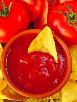 Croustilles jaunes triangulaires et sauce rouge aux tomates
