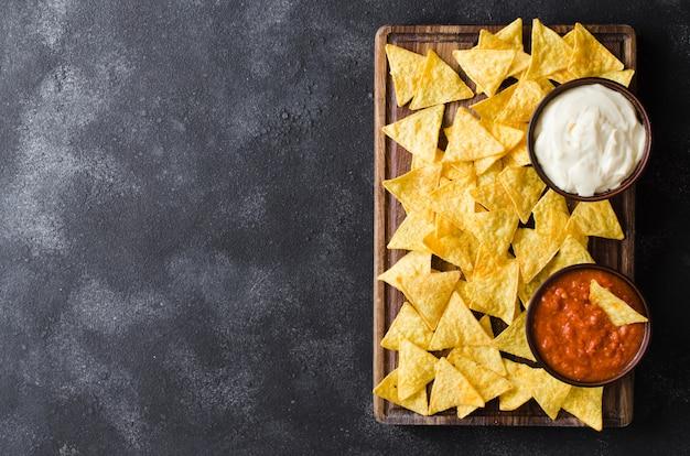 Croustilles de maïs nachos avec sauces épicées à la tomate et au fromage.
