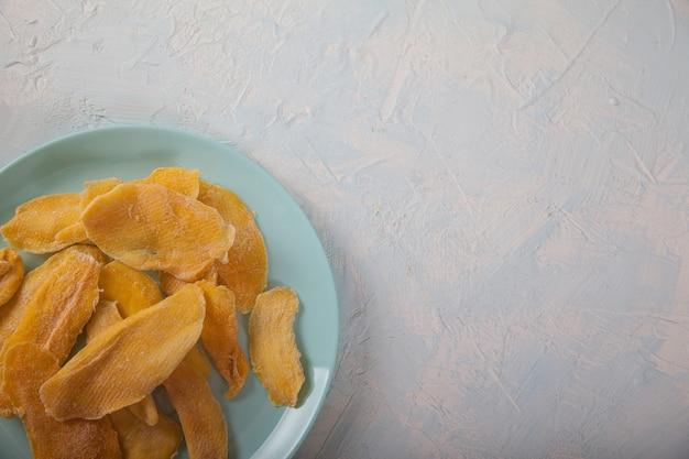 Croustilles de mangue naturelles sur une plaque bleue. mise à plat.