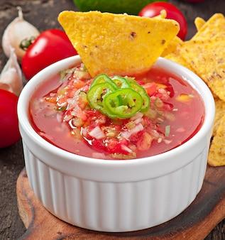 Croustilles de nacho mexicain et trempette de salsa dans un bol sur une surface en bois