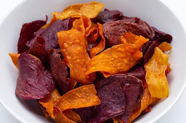 Croustilles de patates douces violettes et jaunes dans un bol
