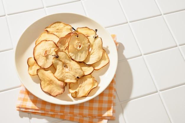 Croustilles de poire sur fond blanc dessert végétalien sans sucre