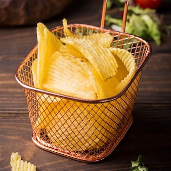 Croustilles de pommes de terre croustillantes dans un panier en cuivre
