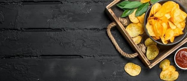 Croustilles avec des sauces dans un plateau en bois. sur fond rustique noir.
