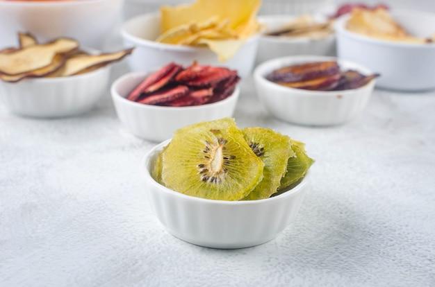 Croustilles séchées assorties et fruits mûrs dans des assiettes sur fond gris. chips de fruits. concept d'alimentation saine, collation, sans sucre. vue de dessus, copiez l'espace.