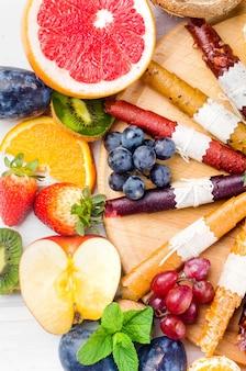 Croustilles séchées assorties et fruits mûrs sur fond gris. chips de fruits. concept d'alimentation saine, collation, sans sucre. vue de dessus, copiez l'espace.