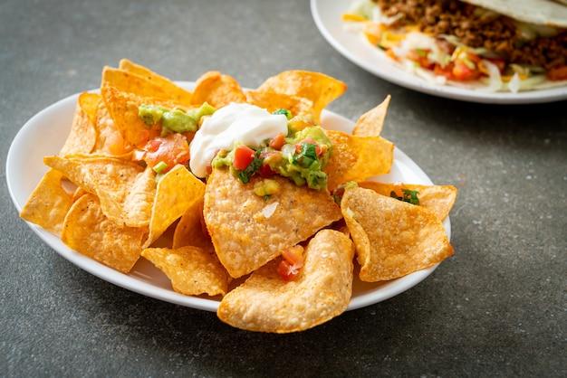 Croustilles de tortilla aux nachos mexicains avec jalapeño, guacamole, salsa de tomates et trempette