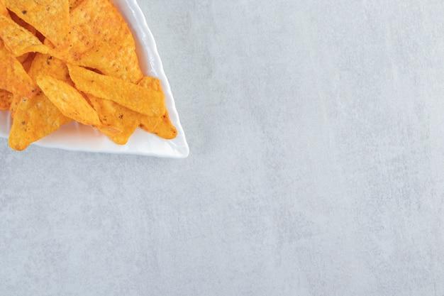 Croustilles tortilla épicées sur plaque en forme de feuille sur pierre