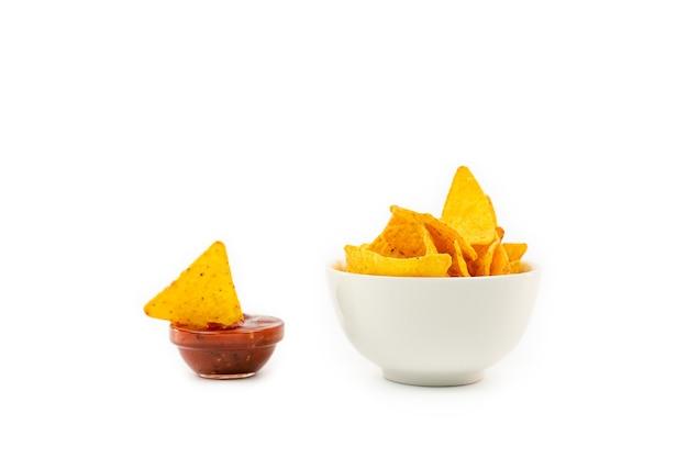 Croustilles tortilla nachos avec sauce isolante dans un bol en céramique.