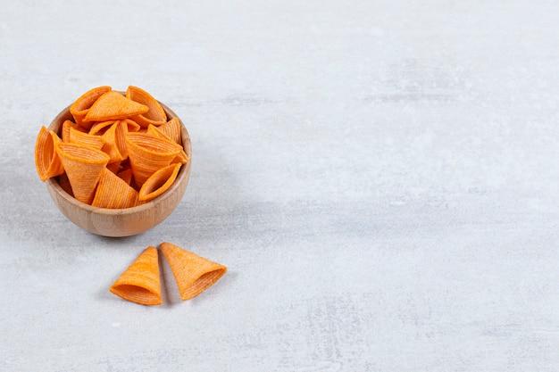 Croustilles de triangle savoureux dans un bol en bois.