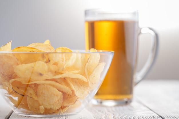 Croustilles et verre de bière sur une table en bois.