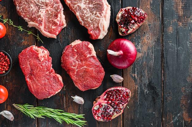Croûte de steaks de boeuf alternative biologique crue, avec des assaisonnements et des herbes sur un vieux fond en bois sombre rustique, vue de dessus avec un espace pour le texte.