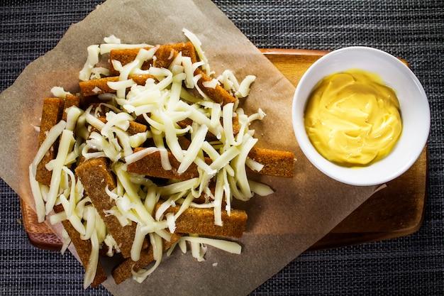 Croûtons de pain de seigle saupoudrés de fromage râpé et de sauce sur une assiette en bois