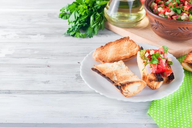 Croûtons avec une salade de tomates et du fromage avec des légumes verts