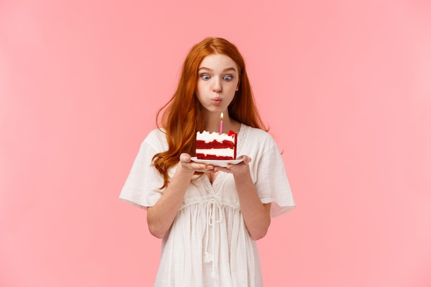 Croyez au miracle. mignonne et idiote rousse souhaitant faire un vœu pour l'anniversaire, souffler la bougie sur le gâteau du jour b avec une expression ciblée, s'amuser, faire la fête et célébrer en cercle familial