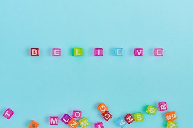 Croyez l'inscription faite de perles de cube colorées avec des lettres. concept de fond bleu festif avec espace de copie.