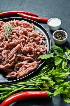 Cru haché sur une plaque noire. ingrédients pour la cuisine, romarin, piment, ail, sel, persil, aneth.