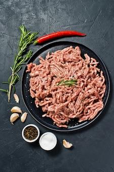 Cru haché sur un plateau en pierre. ingrédients pour la cuisine, romarin, piment, ail, sel.