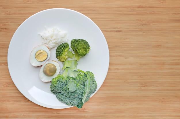 Cru de nourriture pour bébé (brocoli, oeuf et riz) en plaque blanche sur une planche de bois avec espace copie.