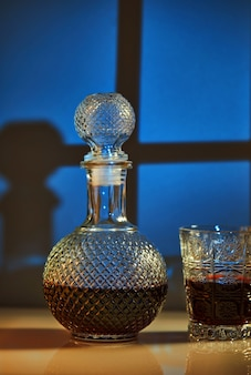 Une cruche avec du vin rouge et un verre de vin, nature morte dans le contexte d'une fenêtre
