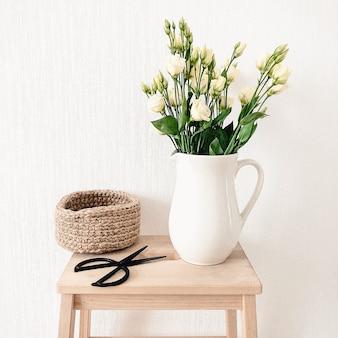 Une cruche de fleurs blanches et un panier décoratif avec des ciseaux noirs sur une surface blanche