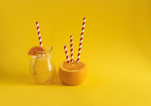 Une cruche de jus d'orange fraîchement pressé et une demi-orange avec des tubes à boire en carton contrastés. fond jaune. concept d'alimentation saine. prévention des maladies avec de la vitamine c. copiez l'espace.