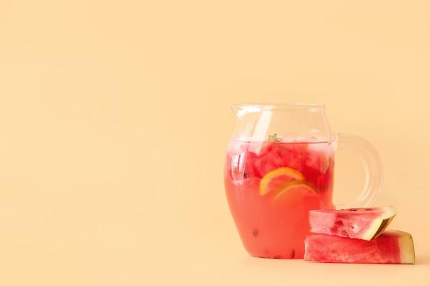 Cruche de limonade froide de pastèque sur la surface de couleur