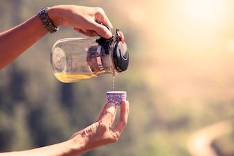 Cruche de thé verser de l'eau de thé dans une tasse dans l'heure du matin dans le filtre de couleur vintage