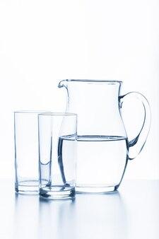 Cruche et verre sur fond blanc.