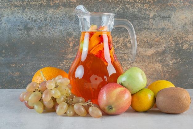 Une cruche en verre de jus avec des fruits sur marbre