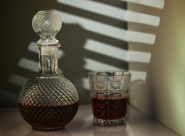 Cruche de vin rouge et verre de vin, avec un éclairage inhabituel sous forme de motifs sur le mur