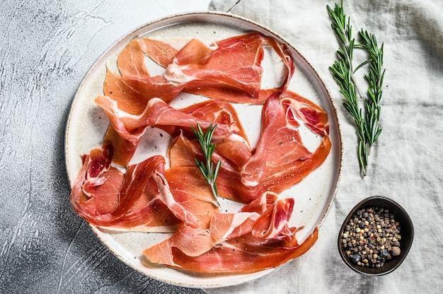 Crudo de prosciutto, salami italien, jambon de parme. assiette antipasti. fond gris, vue de dessus.