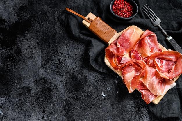 Crudo de prosciutto, salami italien, jambon de parme. assiette antipasti. fond noir, vue de dessus.