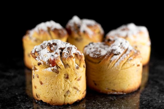 Cruffins, la tendance de la pâtisserie moderne de l'année est le macareux, un mélange de croissants et de cupcakes. sur fond noir saupoudré de sucre en poudre