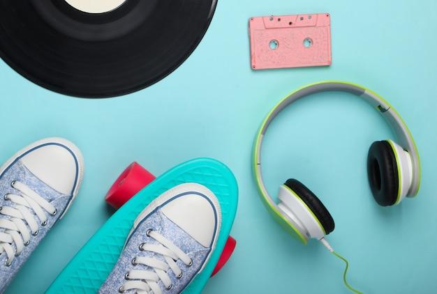 Cruiser board, casque stéréo, cassette audio, disque vinyle sur une surface bleue