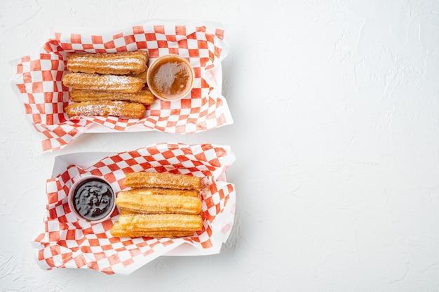 Crullers frits en brun, sac à emporter dans le bac à papier, sur fond blanc, vue de dessus à plat avec un espace pour le texte, copyspace
