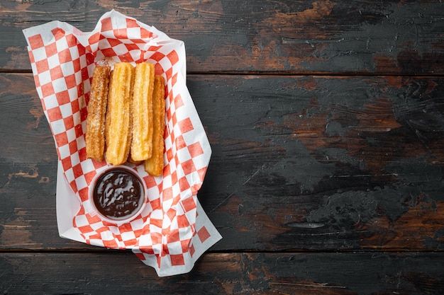 Crullers frits en brun, sac à emporter dans le bac à papier, sur la vieille table en bois sombre