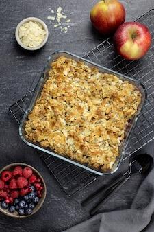 Crumble aux canneberges et aux pommes, croustillant dans un plat de cuisson en verre avec des flocons d'amande et des baies fraîches sur du béton foncé.