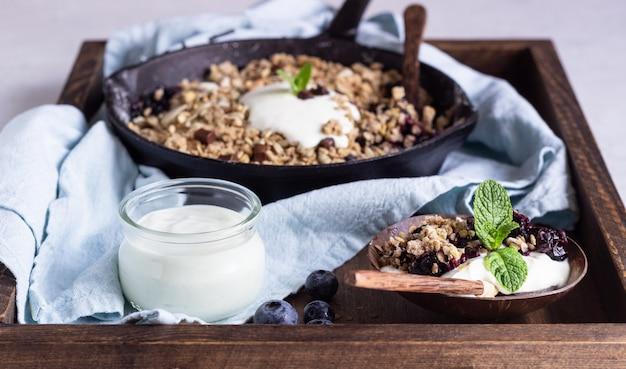 Crumble à l'avoine dans une poêle en fonte avec myrtilles fraîches et yaourt naturel.