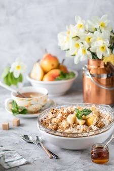 Crumble de poire au four avec des poires et du miel dans un plat blanc sur la table avec des ustensiles en cuivre et des fleurs