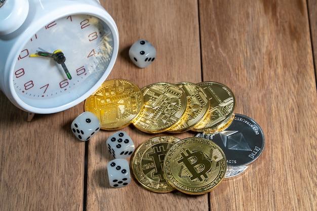 Crypto-monnaie bitcoin, litecoin et dés avec réveil vintage blanc sur la languette en bois