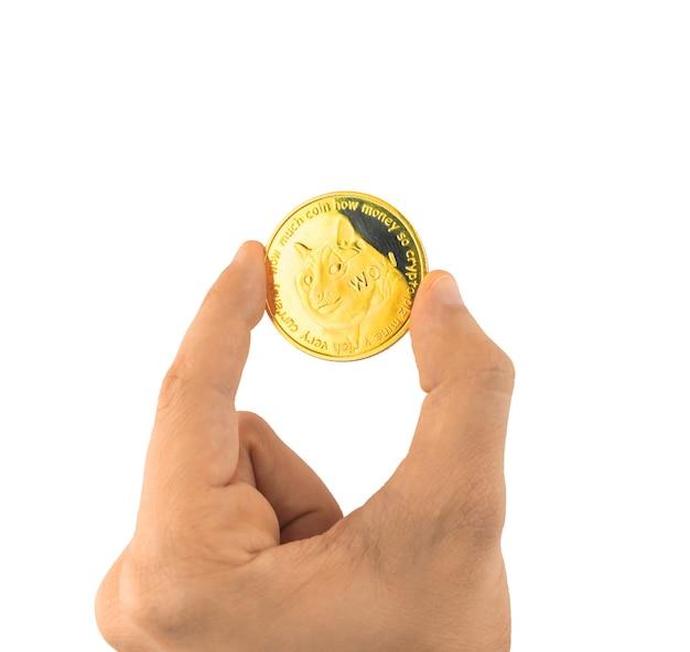 Une crypto-monnaie dogecoin en main masculine, isolée sur fond blanc photo