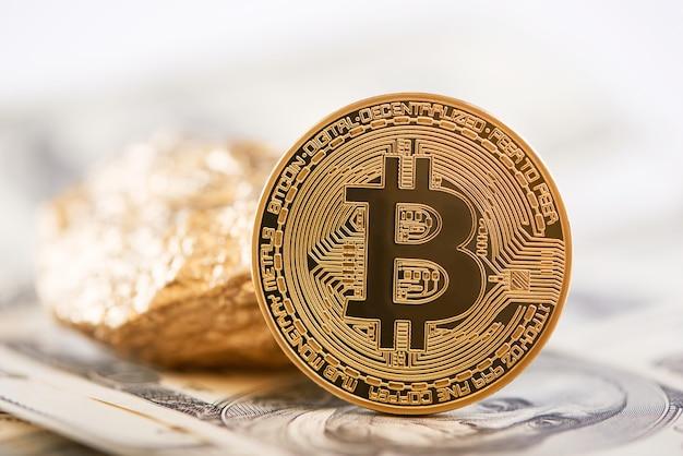 La crypto-monnaie principale, le bitcoin doré et la masse d'or représentée sur l'arrière-plan des billets en dollars.