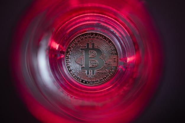 Crypto-monnaie tombant au fond. fond rouge et rétro-éclairage violet. bitcoin dans un verre avec