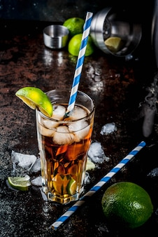 Cuba libre, cocktail long island ou thé glacé avec alcool fort, cola, citron vert et glace, deux verres, espace de copie de surface sombre